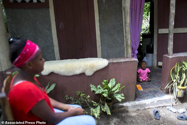 Janila Jean, 18, sits in front of a friend's house as her daughter cries during an interview in Jacmel, Haiti