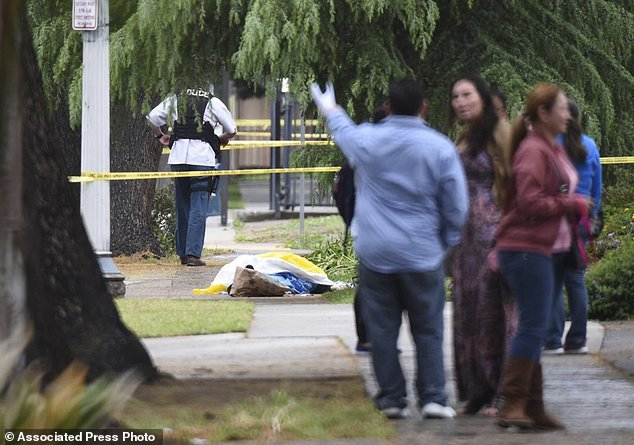 Evacuated office workers stand by with a deceased shooting victim down on the sidewalk in the horror rampage in Fresno