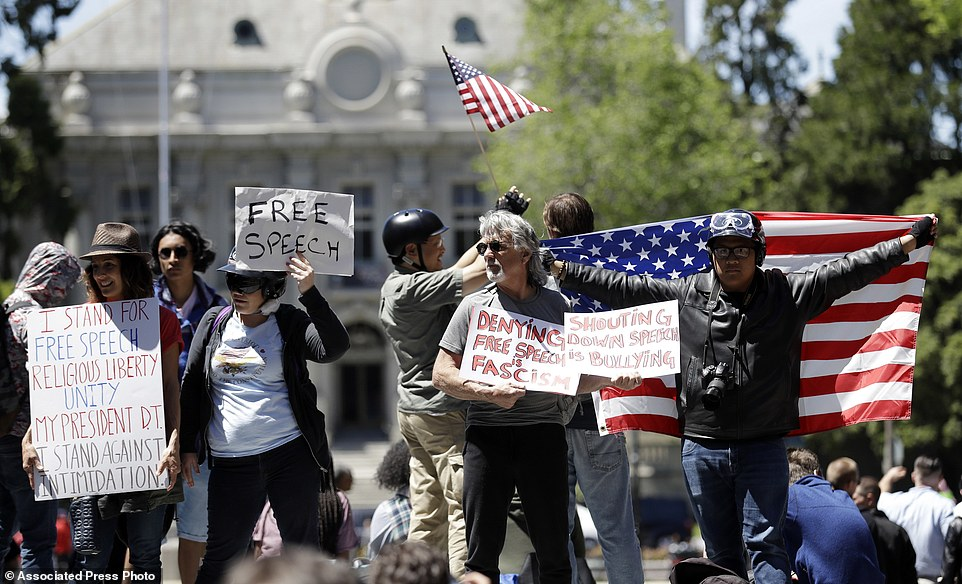Supporters of Ann Coulter hold signs and flags one day after the Berkeley campus canceled her appearance there for fear of violent protests