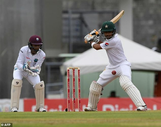 Babar Azam of Pakistan plays a cover shot as West Indies wicketkeeper Shai Hope looks on during the first day of play, of the 3rd and final test match at the Windsor Park Stadium in Roseau, Dominica on May 10, 2017