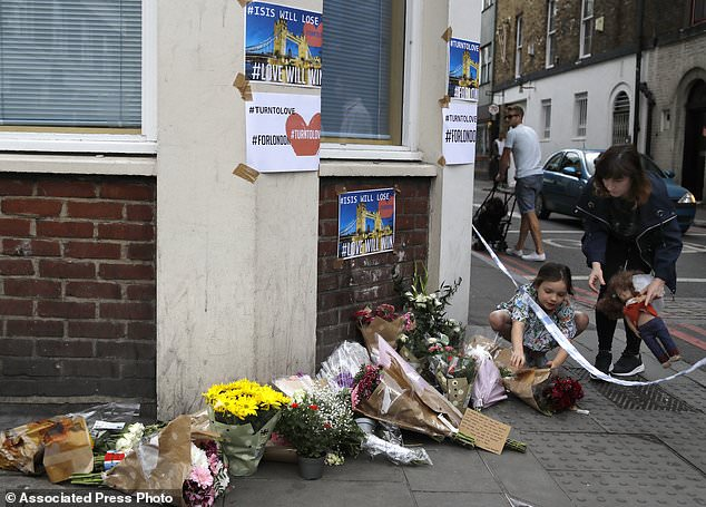 A small child lays flowers at a corner tribute in the London Bridge area of London, Sunday, June 4, 2017. Police specialists collected evidence in the heart of London after a series of attacks described as terrorism killed several people and injured more than 40 others. (AP Photo/Frank Augstein)