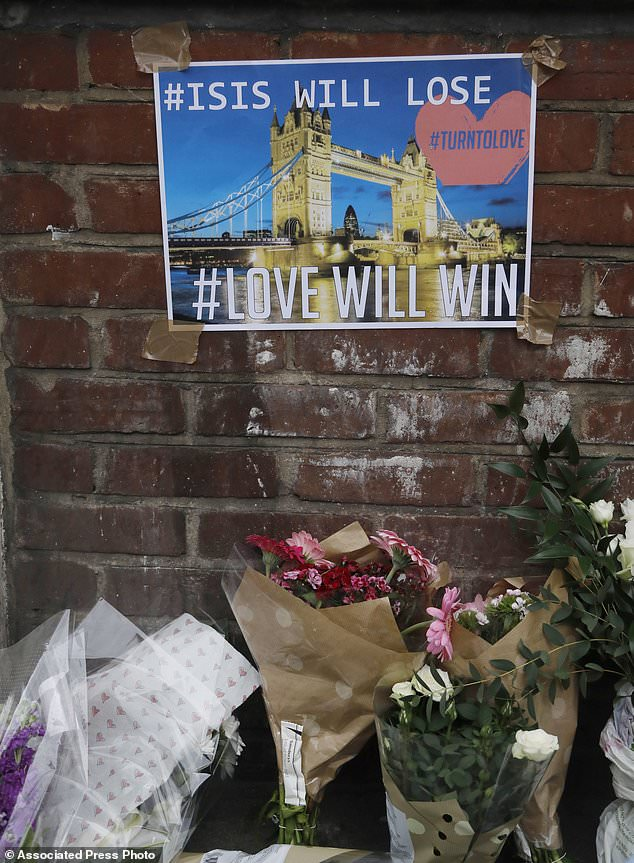 A tribute of flowers has been placed on the pavement and a poster with a photo of London Bridge is taped on a wall in the London Bridge area of London, Sunday, June 4, 2017. Police specialists collected evidence in the heart of London after a series of attacks described as terrorism killed several people and injured more than 40 others. (AP Photo/Frank Augstein)