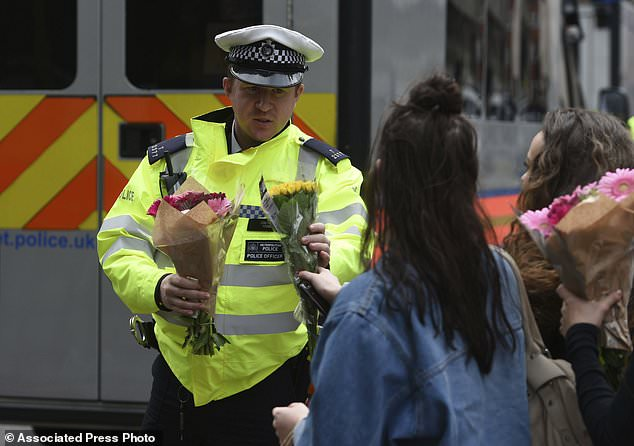A woman hands flowers to a police officer to lay on the north side of London Bridge following last night's terrorist incident, Sunday, June 4, 2017. Police specialists collected evidence in the heart of London after a series of attacks described as terrorism killed several people and injured more than 40 others. (David Mirzoeff/PA via AP)