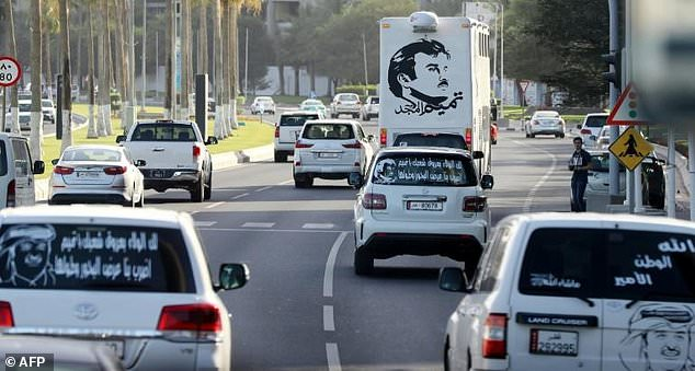 A general view taken in Doha on June 11, 2017 shows portraits of Qatar's Emir Sheikh Tamim bin Hamad Al-Thani on the back of vehicles