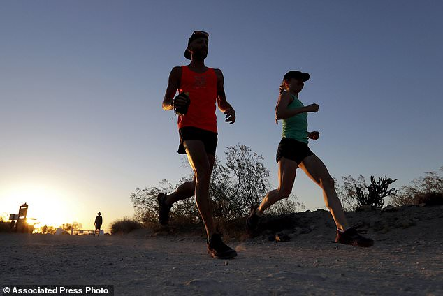 A couple runs through section of South Mountain Park at sunrise to avoid the excessive heat, Friday, June 16, 2017 in Phoenix. Authorities issued a warning about the heat wave, urging people to keep hydrated