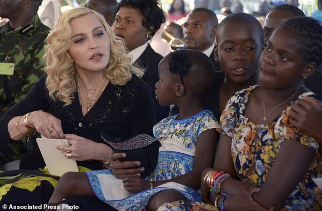 US musician Madonna, left, sits with her adopted children Stella, David and Mercy, at the opening of The Mercy James Institute for Pediatric Surgery and Intensive Care, located at the Queen Elizabeth Central Hospital in the city of Blantyre, Malawi, Tuesday, July 11, 2017. Madonna was in Malawi on Tuesday for the official opening of a hospital children's wing funded by her charity and named after one of the four children the pop star has adopted from the impoverished southern African nation. (AP Photo Thoko Chikondi)