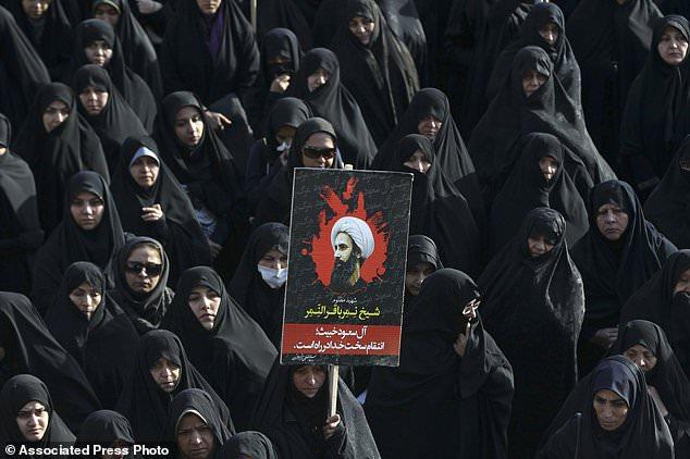 En esta foto de archivo del 4 de enero de 2016, una mujer iraní sostiene un cartel que muestra al jeque Nimr al-Nimr, un destacado clérigo shiita saudita que fue ejecutado por la Arabia Saudita en Teherán, Irán.  El nuevo príncipe heredero de Arabia Saudí espera transformar el reino y modernizar la sociedad, pero la ejecución planeada de 14 manifestantes chiítas acusados de violencia contra las fuerzas de seguridad sugiere que el manejo del reino de tensiones sectarias y disturbios permanece inalterado.  (AP Photo / Vahid Salemi, Archivo)