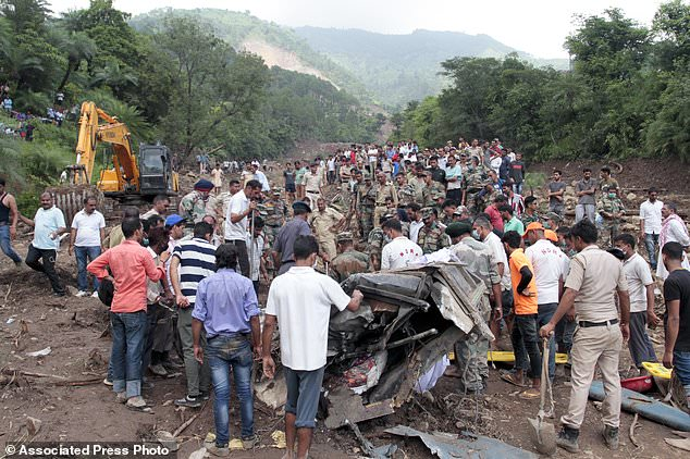 People watch army soldiers and rescue workers recover bodies of landslide victims even as they try to pull out two buses that were covered in mud after a landslide triggered by heavy monsoon rain in Urla village, Himachal Pradesh state, India, Sunday, Aug. 13, 2017. The landslide that occurred early Sunday buried part of a highway, trapping two buses and at least three cars. (AP Photo/Shailesh Bhatnagar)