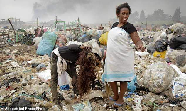 In this photo taken Wednesday, Aug. 23, 2017, Winnie Wanjira, 31, is offered hair pieces to buy by a man who collects them from the piles of rubbish, at the Dandora municipal dumpsite in Nairobi, Kenya. In one of Africa's largest dumps, some residents are making a living by collecting and recycling hair from the mountains of rubbish. (AP Photo/Adelle Kalakouti)