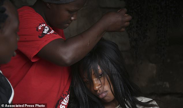 In this photo taken Thursday, Aug. 24, 2017, hairdresser Mary Wanjiku, 29, weaves the hair of local resident Ruth Njera, 25, at a makeshift hair salon in the Korogocho slum of Nairobi, Kenya. In one of Africa's largest dumps, some residents are making a living by collecting and recycling hair from the mountains of rubbish. (AP Photo/Adelle Kalakouti)