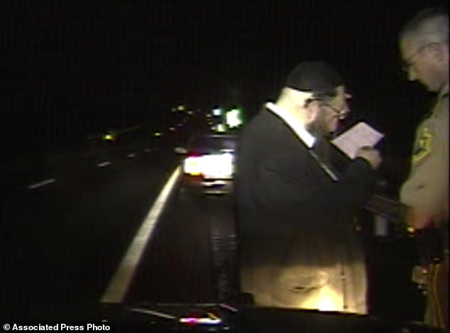 Trooper Justin Thompson, right, watches driver Rabbi Berl Fink read a citation. An internal investigation of the nighttime traffic stop  has cleared the trooper of wrongdoing