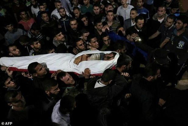 The body of Palestinian Marwan Alagha, 22, is carried by mourners in the Gaza Strip after he was killed when Israel blew up what it said was a tunnel stretching from Gaza into its territory