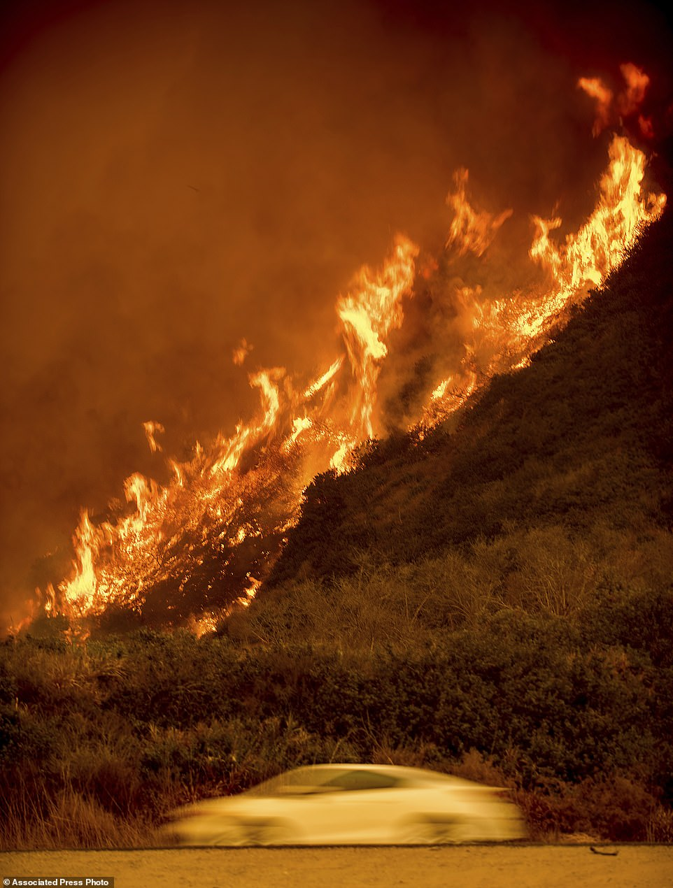 Flames from the Thomas fire burn above traffic on Highway 101 north of Ventura. Scenes similar to this were glimpsed across the state as people tried to go about their lives in the face of the fire