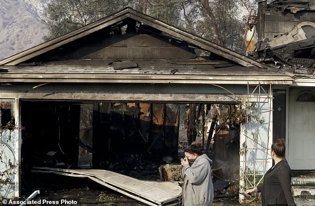 Neighbors walk past a home destroyed by wildfire along Via San Anselmo in the Sylmar area of Los Angeles Wednesday, Dec. 6, 2017. (AP Photo/Chris Carlson)