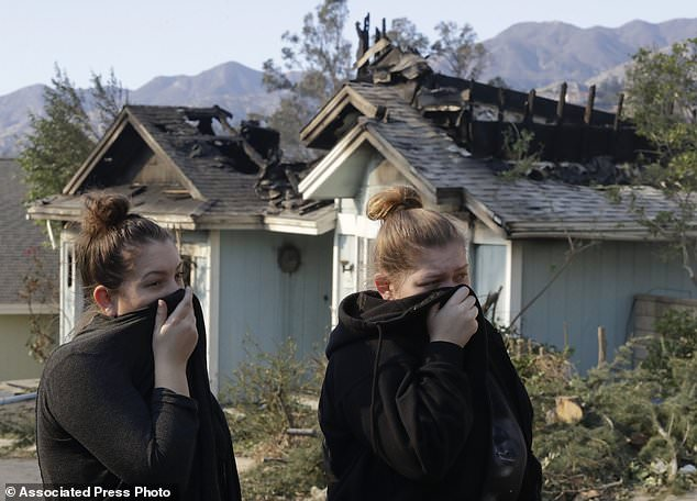 Crystal Shore, left, and her sister Carrie look over the damage to their neighbor's home along Via San Anselmo in the Sylmar area of Los Angeles Wednesday, Dec. 6, 2017. (AP Photo/Chris Carlson)