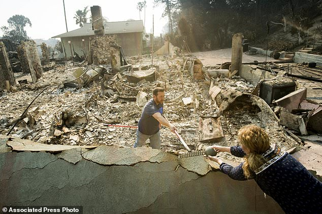 Paul Mattesich hands a jar to his wife Erica Mattesich while sifting through rubble at his family's Ventura, Calif., home following a  wildfire on Wednesday, Dec. 6, 2017. (AP Photo/Noah Berger)