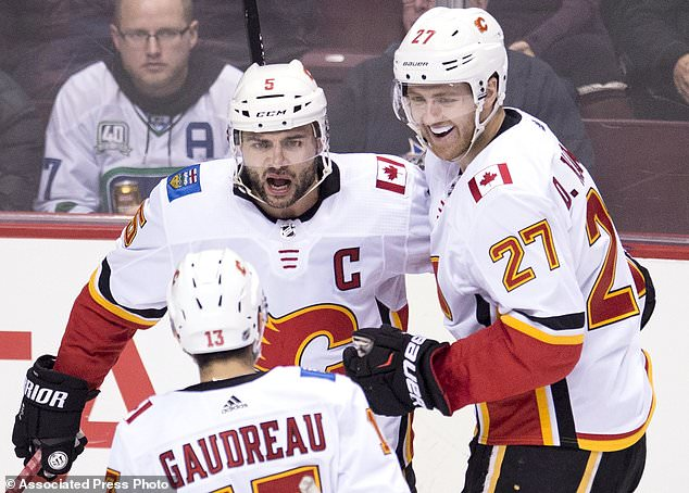 Calgary Flames defenceman Mark Giordano (5) celebrates his goal with teammates Johnny Gaudreau (13) and Dougie Hamilton (27) during second period NHL hockey action in Vancouver, British Columbia, Sunday, Dec. 17, 2017. (Jonathan Hayward/The Canadian Press via AP)