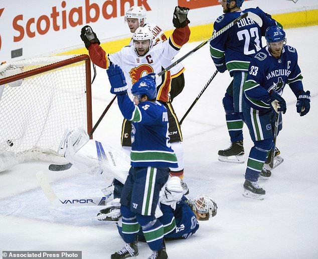 Calgary Flames defenseman Mark Giordano (5) celebrates his goal past Vancouver Canucks goalie Jacob Markstrom (25) during second period NHL hockey action in Vancouver, British Columbia, Sunday, Dec. 17, 2017. (Jonathan Hayward/The Canadian Press via AP)