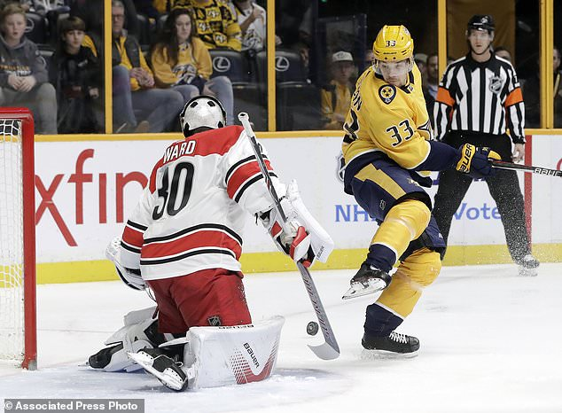 Nashville Predators left wing Viktor Arvidsson (33), of Sweden, gets out of the way of a shot against Carolina Hurricanes goalie Cam Ward (30) during the second period of an NHL hockey game Thursday, Dec. 21, 2017, in Nashville, Tenn. (AP Photo/Mark Humphrey)