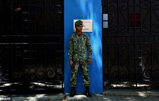 A Maldives soldier stands guard outside the presidential residence in Male as President Abdulla Yameen refused Thursday to meet senior European diplomats