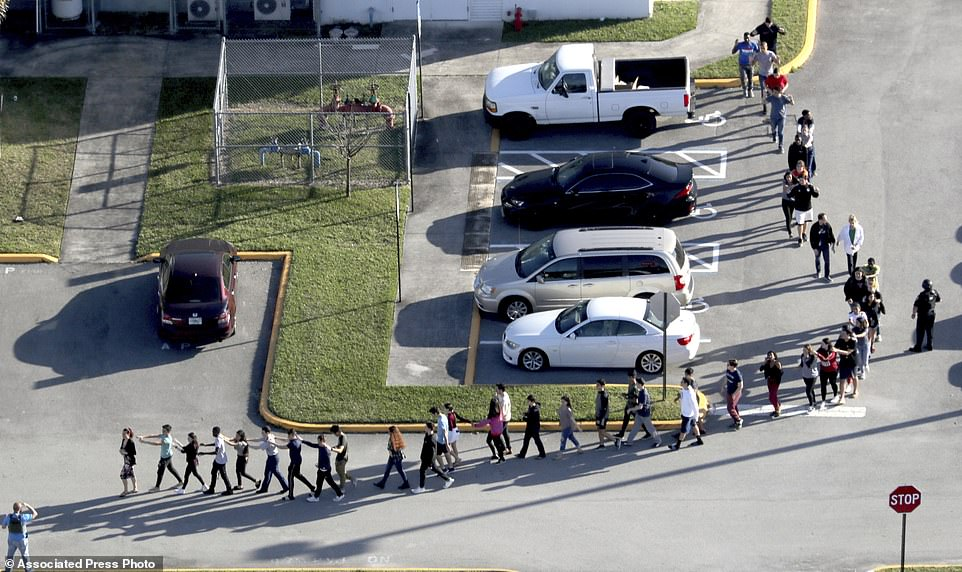 Students are evacuated by police from Marjory Stoneman Douglas High School in Parkland, Fla., on Wednesday, Feb. 14, 2018, after a shooter opened fire on the campus