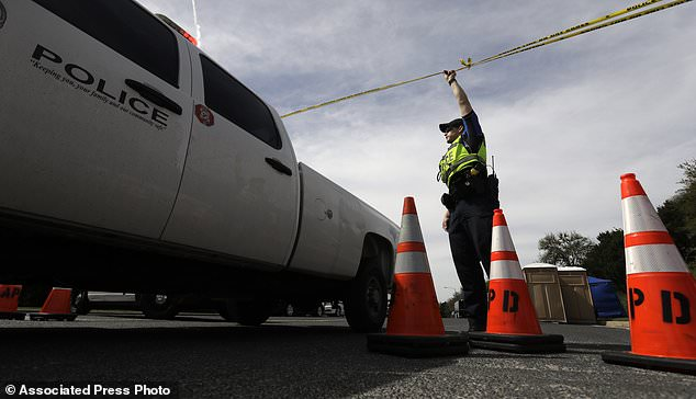 An Austin police officer raises a barrier near the site of Sunday's explosion, Monday, March 19, 2018, in Austin, Texas. Multiple people were injured in the explosion Sunday night, and police warned nearby residents to remain indoors overnight as investigators looked for possible links to other package bombings elsewhere in the city this month. (AP Photo/Eric Gay)