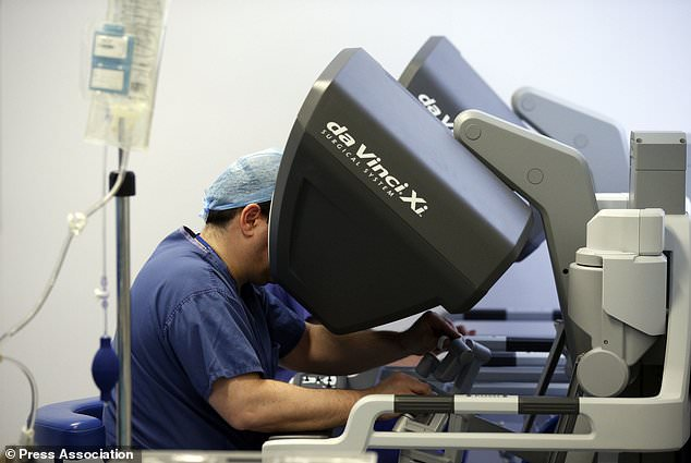 Surgeons sit at opposite ends of a robotic console while they perform the operation