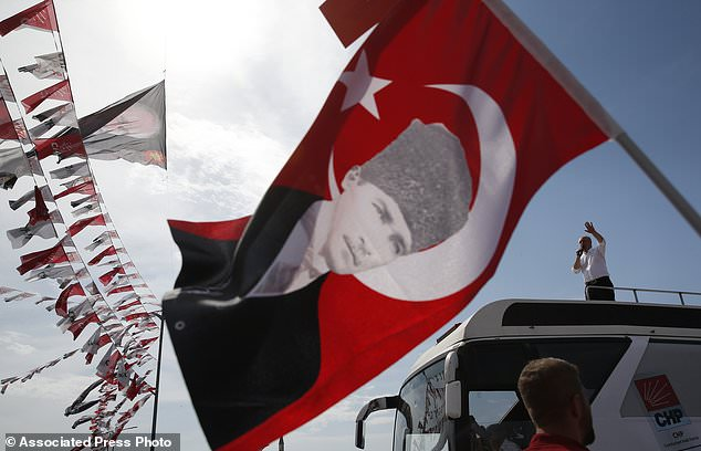 FILE - In this Saturday, June 16, 2018 file photo, a supporter waves a Turkish flag decorated with a picture of Turkish Republic founder Mustafa Kemal Ataturk, as Muharrem Ince, the presidential candidate of Turkey's main opposition Republican People's Party, delivers a speech at a rally ahead of the June 24 elections, in Istanbul. The combative 54-year-old former physics teacher is seen as a strong contender to end Turkey's President Recep Tayyip Erdogan's 16 year rule. (AP Photo/Lefteris Pitarakis)