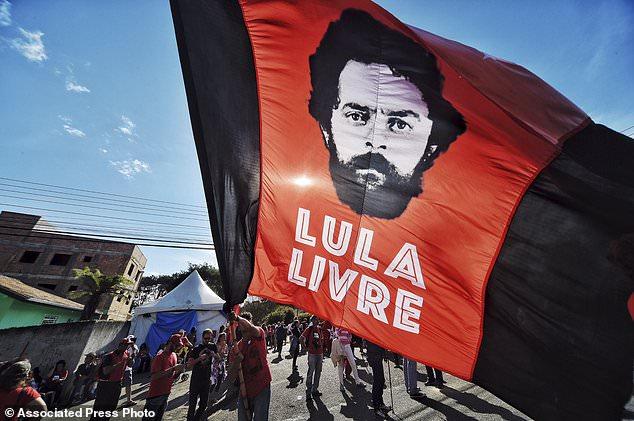 Un supporter de l'ex-président Luiz Inacio Lula da Silva tient un drapeau qui se lit en portugais: