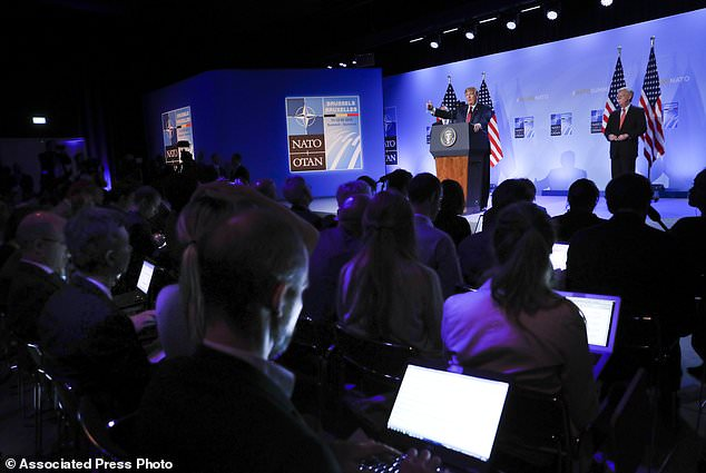 U.S. President Donald Trump gestures while speakings during a news conference before departing the NATO Summit in Brussels, Belgium, Thursday, July 12, 2018. With Trump on stage are Secretary of State Mike Pompeo, behind Trump, and National security adviser John Bolton, right. (AP Photo/Pablo Martinez Monsivais)