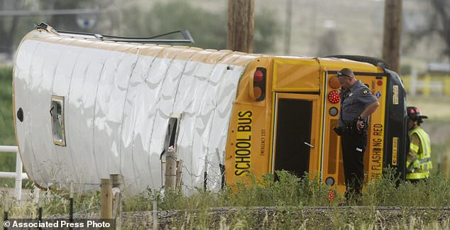 A Weld County Sheriffs Deputy talks on the phone at the scene of a crash involving a school bus on Thursday, July 12. 2018.