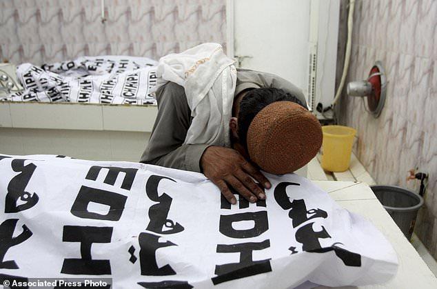 Un pakistanais pleure un cadavre d'un membre de sa famille tué dans un attentat à la bombe dans une morgue à Quetta, au Pakistan, vendredi 13 juillet 2018. Soulignant la menace à la sécurité, deux bombes ont explosé vendredi tuant beaucoup de gens lors des dernières élections la violence liée à frapper le Pakistan. La première bombe qui a tué quatre personnes a explosé dans le nord-ouest du Pakistan près du rassemblement électoral d'un haut responsable politique d'un parti islamiste qui se présente au parlement de la ville de Bannu, au nord-ouest du pays. (Photo AP / Arshad Butt)