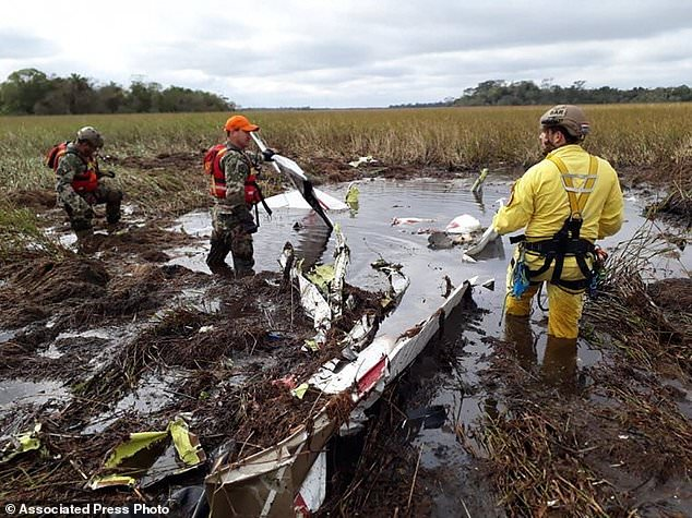 Rescue workers search the crash site of a twin-engine Beechcraft Baron in Ayolas, Paraguay, Thursday, July 26, 2018. Paraguay's agriculture minister and three other people have died in the crash of the small plane, that went down in a marshy area shortly after taking off Wednesday night from the airport in Ayolas. (Photo by Roque Gonzalez Vera/ABC Color via AP)