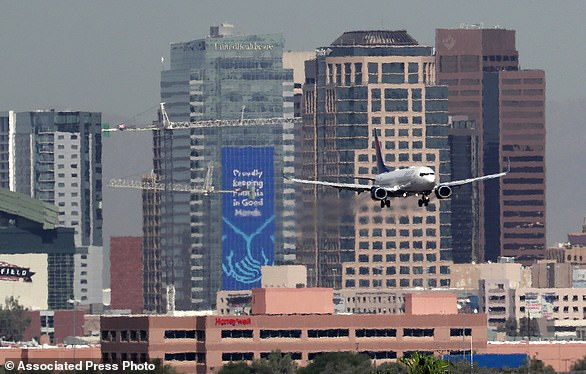 Heat ripples blur the downtown skyline as a jet lands in Phoenix, Ariz., as temperatures exceed 100 degrees in the morning hours. Already devilishly hot for being in the Sonoran desert, Arizona's largest city is also an 'urban heat island,' a phenomenon that pushes up temperatures in areas covered in heat-retaining asphalt and concrete.
