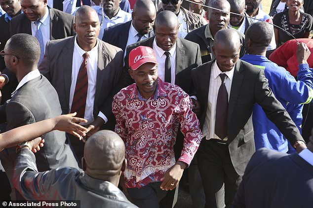 Nelson Chamisa, center, head of the MDC opposition alliance arrives for a rally in Chitungwiza about 30 kilometres east of the capital Harare, Thursday, July, 26, 2018. Chamisa addressed his first rally since rejecting the idea of boycotting elections on Monday despite what he calls a biased election commission, in the first election since the November resignation of longtime leader Robert Mugabe. (AP Photo/Tsvangirayi Mukwazhi)