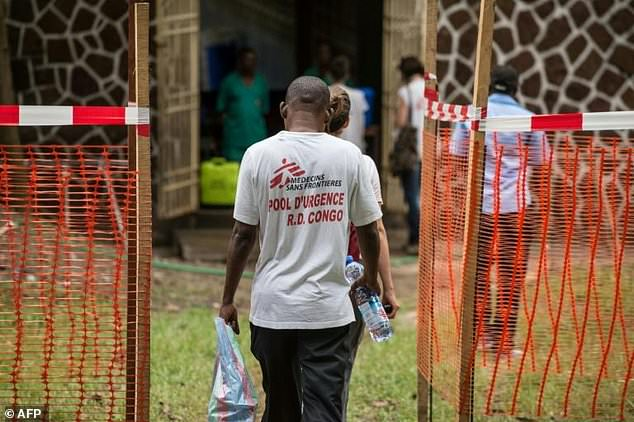 Officials in the African nation have confirmed three deaths so far (pictured: Doctors Without Borders team members walk through an Ebola security zone at the entrance of a hospital in DR Congo, where a fresh outbreak of the virus was declared in the east of the country)