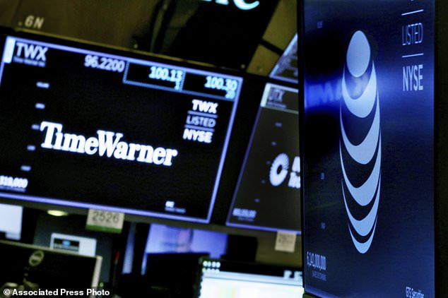 FILE - In this June 13, 2018, file photo, the logos for Time Warner and AT&T appear above alternate trading posts on the floor of the New York Stock Exchange. The Trump Justice Department says it proved that AT&T's mega-merger with Time Warner will hurt competition, and the judge who allowed the takeover was clearly wrong to conclude consumers wouldn't be harmed. The government's argument came in its brief filed Monday, Aug. 6, 2018, with a federal appeals court. (AP Photo/Richard Drew, File)