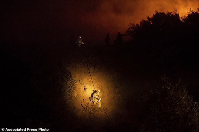 Firefighter Brandon Esquer walks down a hill near Ladoga, California on Tuesday, August 7, 2018 while battling the Ranch Fire, part of the Mendocino Complex Fire. (AP Photo / Noah Berger)