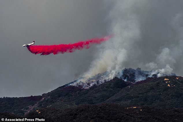 A plane detonates while firefighters at the Cleveland National Forest near Corona, California continue a forest fire on Tuesday, August 7, 2018. Firefighters work in harsh terrain under scorching temperatures that warned of excessive heat and extreme fire, putting much of the region at risk. (Watchara Phomicinda / The Orange County Register via AP)