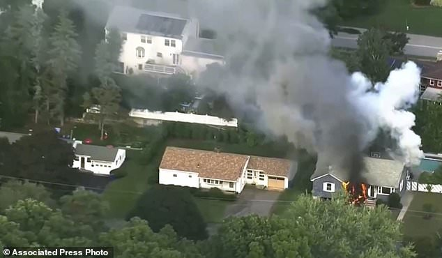 In this image from the video of WCVB in Boston, flames flare from a house in Lawrence, Mass, a suburb of Boston, Thursday, September 13, 2018. Emergency teams respond to what they believe is a series of gas explosions that have Houses damaged in three communities north of Boston. (WCVB via AP)