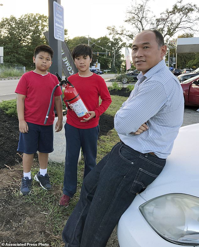 Ra Nam, on the right, with his sons Evan, left, and Tristan, center, were waiting in a parking lot outside their Colonial Heights neighborhood, evacuated on Thursday, September 13, 2018, in Lawrence, Massachusetts because of fires and explosions through a problem with a gas pipeline that supplies homes in several communities north of Boston. (AP Photo / Phil Marcelo)