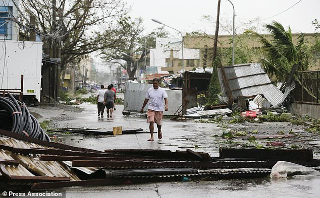 A resident walks beside toppled structures in Tuguegarao city (AP Photo/Aaron Favila)