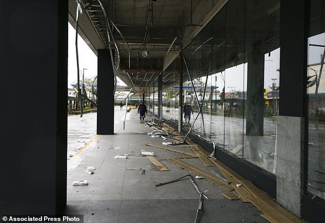 Workers clean up debris outside a mall that got partially damaged by strong winds from Typhoon Mangkhut as it barreled across Tuguegarao city in Cagayan province, northeastern Philippines on Saturday, Sept. 15, 2018. The typhoon slammed into the Philippines northeastern coast early Saturday, it's ferocious winds and blinding rain ripping off tin roof sheets and knocking out power, and plowed through the agricultural region at the start of the onslaught. (AP Photo/Aaron Favila)