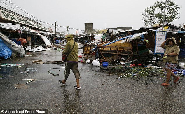 Residents walk beside damaged stalls outside a public market due to strong winds as Typhoon Mangkhut barreled across Tuguegrao city in Cagayan province, northeastern Philippines on Saturday, Sept. 15, 2018. The typhoon slammed into the Philippines northeastern coast early Saturday, it's ferocious winds and blinding rain ripping off tin roof sheets and knocking out power, and plowed through the agricultural region at the start of the onslaught. (AP Photo/Aaron Favila)