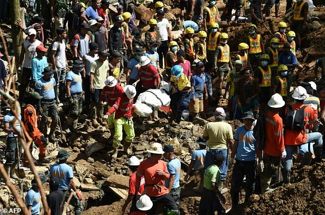 Rescuers carry a body bag from the Philippines landslide site where dozens are feared buried