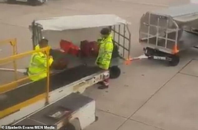 His co-worker stands and watches the suitcases bounce off the cart onto the ground - but doesn't bat an eyelid