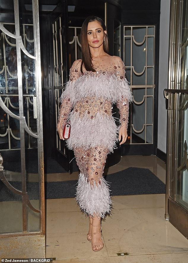 Brünette Schönheit: Cheryl beendete den Look, indem sie ihre glänzenden Kastanienschlösser in einem schlanken Seitenscheitel umrahmte, der ihre hübschen Gesichtszüge umrahmte, während sie eine schillernde, scharlachrote Clutch-Tasche trug
