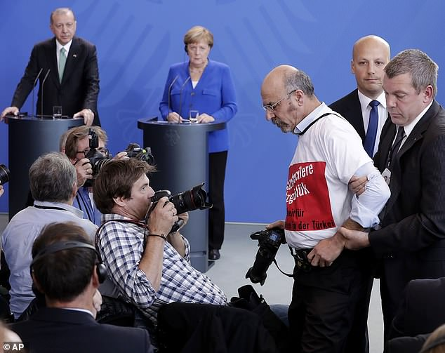 A protester is removed from the joint press conference held by the Turkish and German leaders in Berlin