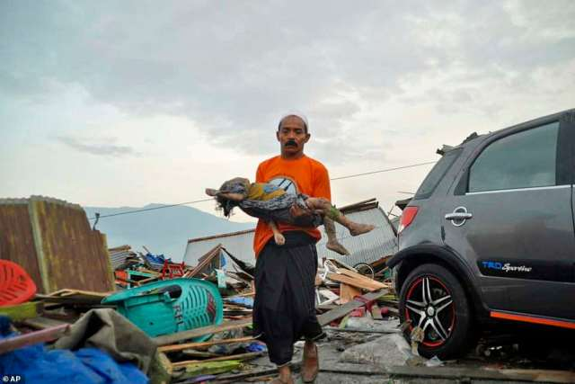 A man carries the body of a child who was killed in the tsunami. Rescue efforts have been hindered by power outage on the Island