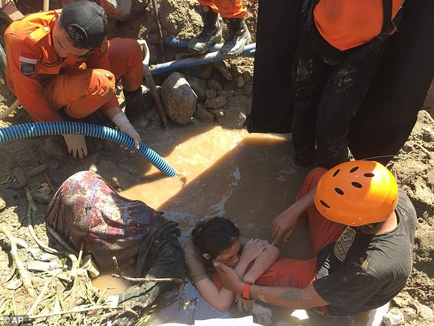 A team of rescuers helping to pull a trapped woman from the mud on Sunday